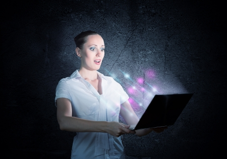 stress testing: young attractive woman holding a laptop, it shines and depart monitor lights