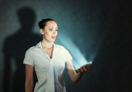 young attractive woman holding a cell phone in a dark room at her glow from the monitor Stock Photo