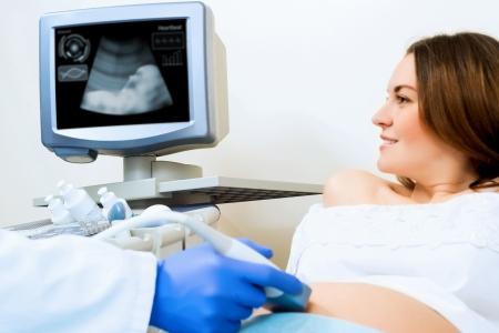 prueba de embarazo: joven mujer embarazada en el ultrasonido, chequeo de salud Foto de archivo