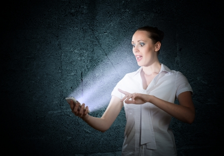 stress testing: young attractive woman holding a cell phone in a dark room at her glow from the monitor Stock Photo