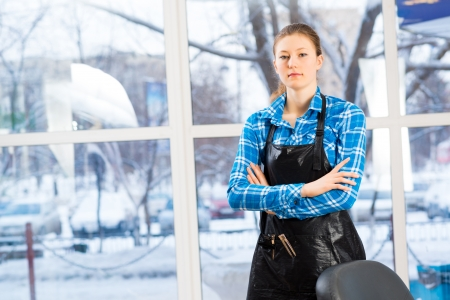 horizontal haircut: portrait of a woman in a barber shop barber worth apron crossed her arms Stock Photo