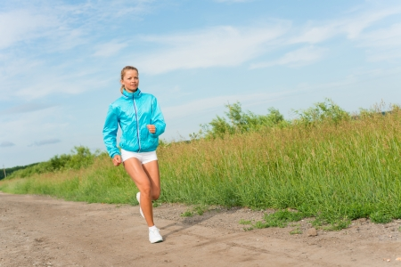 young woman running along a rural road, exercise outdoors photo