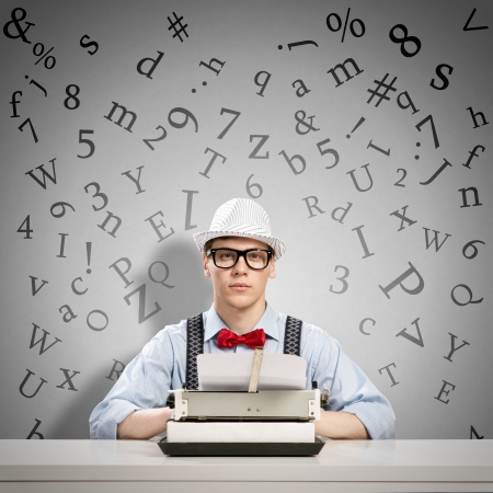 image of a young journalist, sitting at the table for a typewriter Stock Photo