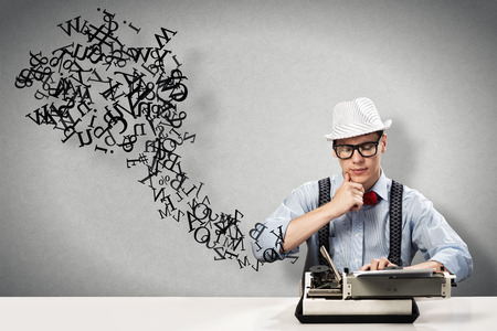 crazy man: image of a young journalist, sitting at the table for a typewriter Stock Photo