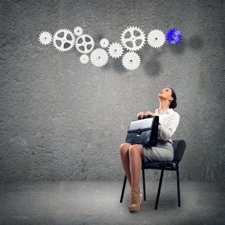 image of a beautiful young business woman sitting on a chair and looking at the gears on photo