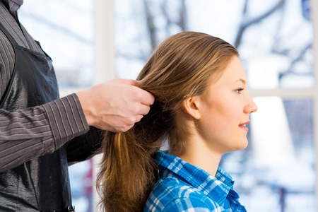 coiffeur: male hairdresser puts woman s hair in a hairdressing salon