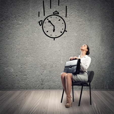 image of a young business woman looking at the sketched clock photo