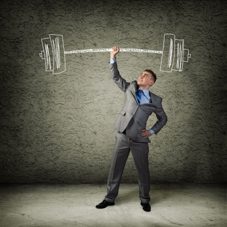 businessman holding a hand sketched barbell, concept achievements in business photo