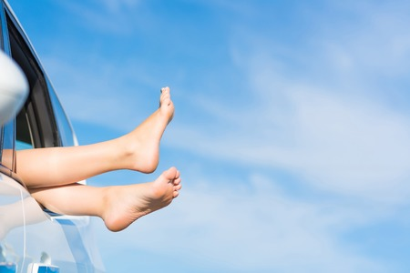 Füße eines jungen Mädchens aus dem Fenster eines Autos auf einem Hintergrund des blauen Himmels