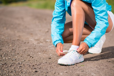 young woman tying shoelaces on sneakers on a rural road, exercise outdoors photo