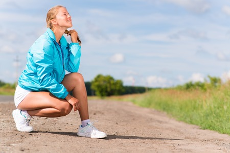 young woman resting after jogging on a rural road photo