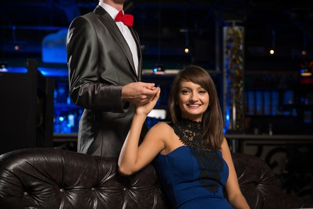 respectable: portrait of a respectable woman sitting on a couch and holding the hand of a man