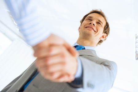 young businessman shaking hands with a colleague, an agreement photo