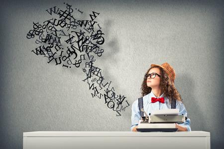 Bild einer jungen Frau, die Schriftstellerin am Tisch mit Schreibmaschine