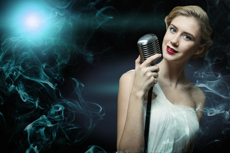 attractive female singer with a microphone behind her abstract background photo