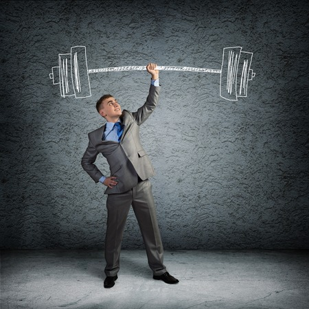 businessman holding a hand sketched barbell, concept achievements in business Stock Photo