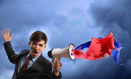 businessman shouting into a megaphone, the concept of aggression in business photo
