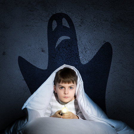 image of a boy under the covers with a flashlight the night afraid of ghosts photo