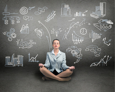 business woman meditating on floor, wall charts and diagrams are drawn Stock Photo