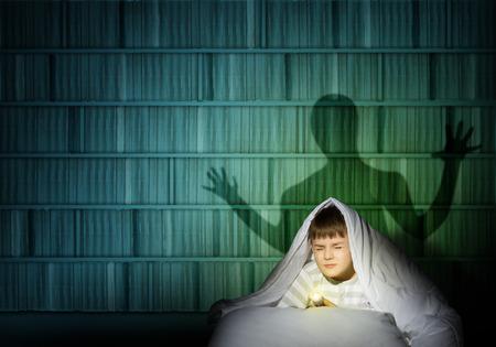 beeld van een jongen onder de dekens met een zaklamp in de nacht bang voor spoken Stockfoto