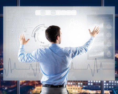 businessman working with modern virtual technologies, stands back, hands touching the screen photo
