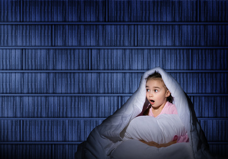 image of a frightened girl under the covers with a flashlight photo