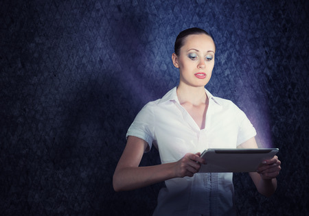 stress testing: young attractive woman holding a tablet in a dark room at her glow from the monitor