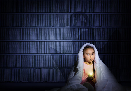 image of a girl under the covers with a flashlight the night afraid of ghosts Imagens