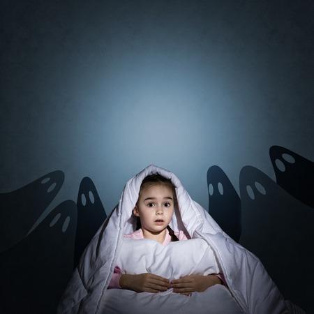 beeld van een meisje onder de dekens met een zaklamp in de nacht bang voor spoken Stockfoto