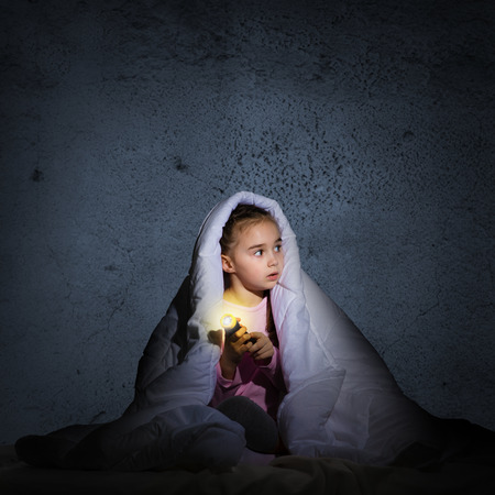 image of a frightened girl under the covers with a flashlight