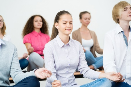 group of young people meditating in office at desk, group meditation