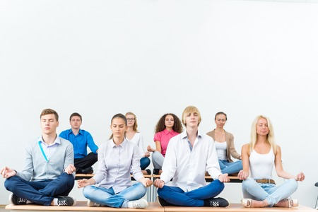 Group Of Young People Meditating In Office At Desk, Group Meditation Photo