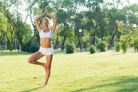 active lifestyle: young attractive woman doing yoga in the park, active lifestyle