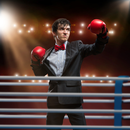 boxing ring: image of a businessman with boxing gloves in the ring, the competition in the business Stock Photo