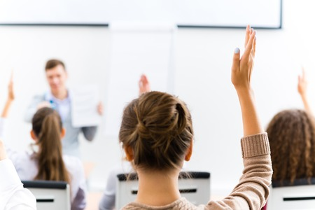answer: image of a female hand raised in university classroom Stock Photo