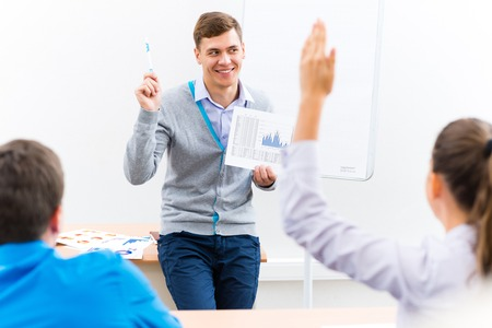 young teacher man talking with students in the classroom