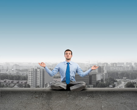image of a businessman meditating on a concrete parapet photo