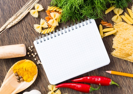 spices, pasta and vegetables around notebook on a wooden table photo