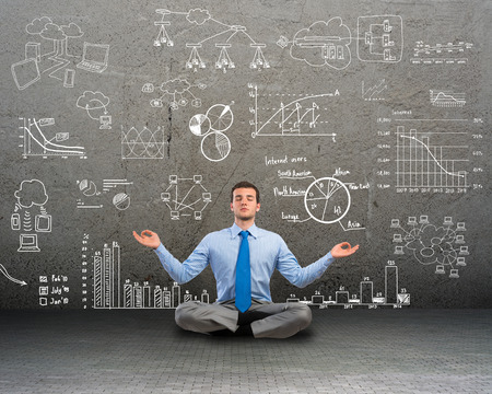 image of a business man meditating on floor, wall charts and diagrams are drawn Stock Photo