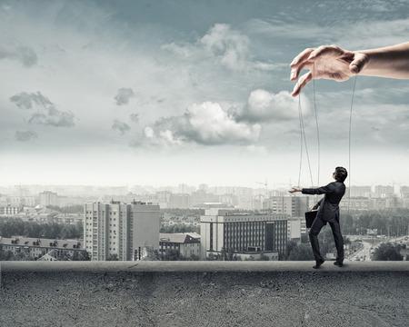 obedecer: hombre de negocios de títeres camina sobre el parapeto de concreto Foto de archivo