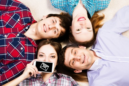 four young men lie together, young attractive woman pressed her lips to the phone photo