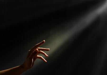conceptueel beeld van het streven naar vrijheid vrouw s hand bereikt voor de lichtstralen, Stockfoto