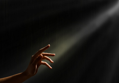 reaches: woman s hand reaches for the light rays, conceptual image of striving for freedom