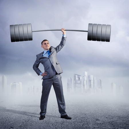businessman holding a barbell with one hand photo