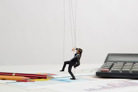 businessman puppet doll is on the desk, past the stationery items photo