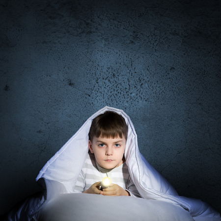 image of a frightened boy under the covers with a flashlight photo