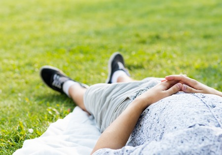 linked hands: man relaxing in the park, close-up of linked hands on his stomach