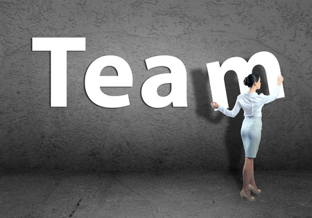 adds: young businesswoman adds team word on concrete wall Stock Photo