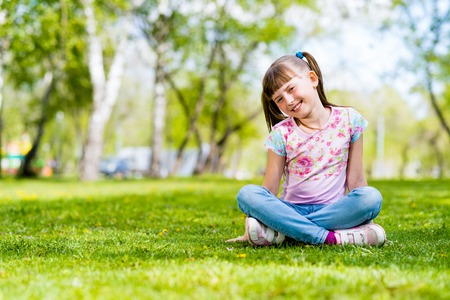 girl sitting in the grass on a summer park photo