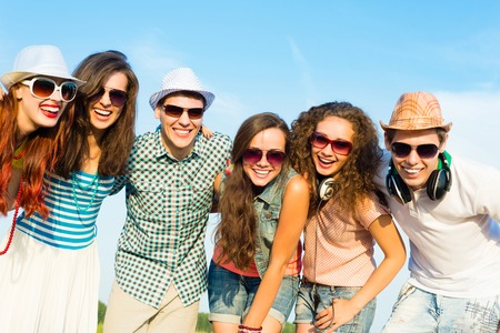 friends hugging: group of young people wearing sunglasses and hats hugging and standing in a row, spending time with friends